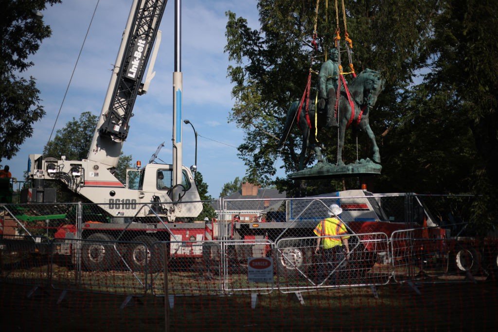 """CHARLOTTESVILLE, VIRGINIA - JULY 10: Workers remove a statue of Confederate General Robert E. Lee from Market Street Park July 10, 2021 in Charlottesville, Virginia. Initial plans to remove the statue four years ago sparked the infamous """"Unite the Right"""" rally where 32 year old Heather Heyer was killed. A statue of Confederate General Thomas """"Stonewall"""" Jackson in the Charlottesville and Albemarle County Courthouse Historic District is also scheduled to be removed this weekend. (Photo by Win McNamee/Getty Images)"""
