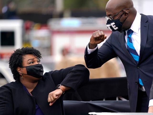 ATLANTA, GA - DECEMBER 15: U.S. Democratic Senate candidate Raphael Warnock (R) bumps elbows with Stacey Abrams (L) during a campaign rally with U.S. President-elect Joe Biden at Pullman Yard on December 15, 2020 in Atlanta, Georgia. Biden's stop in Georgia comes less than a month before the January 5 runoff election for Senate candidates Jon Ossoff and Raphael Warnock as they try to unseat Republican incumbents Sen. David Perdue and Sen. Kelly Loeffler. (Photo by Drew Angerer/Getty Images)