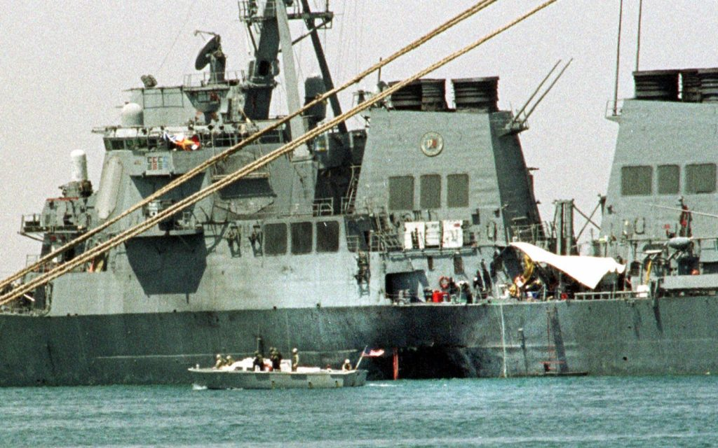 A small boat guards the USS Cole in Aden, Yemen Friday Oct. 20 2000. Investigators have found bomb-making equipment in an apartment near the Yemeni port and believe two former occupants may have carried out the suicide bomboing that killed 17 sailors aboard the USS Cole. (AP Photo/Hasan Jamali)