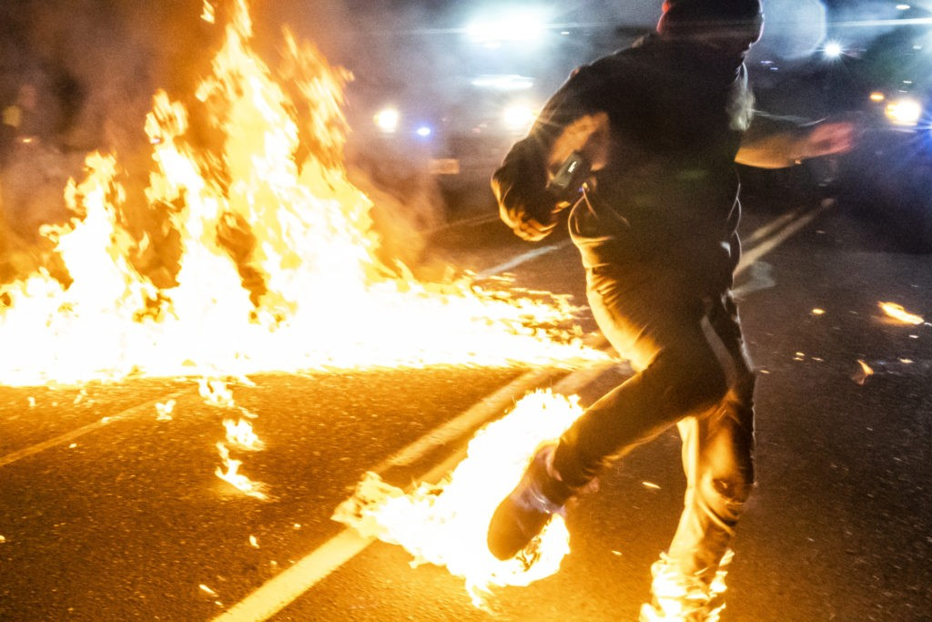 A protester, whos feet caught fire after a molotov cocktail exploded on him, runs toward a medic during a protest on September 5, 2020 in Portland, Oregon. (Nathan Howard/Getty Images)